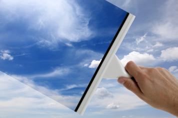 Mytí okna pomocí stěrky a modrá obloha v pozadí