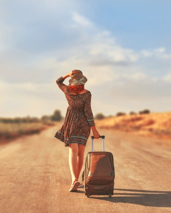 woman-walking-road-with-luggage-freedom-concept_72464-283