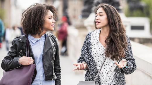 Two female friends talking outdoors in Paris, France